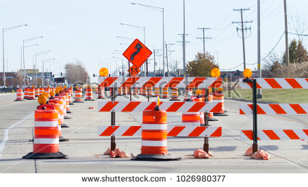 stock-photo-orange-barrels-barricades-and-signs-blocking-a-road-1026980377